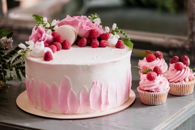 Bolo e cupcakes. barra de chocolate. um bolo de creme de férias rosa decorado com flores e frutas. e cupcakes decorados com framboesas Foto Premium
