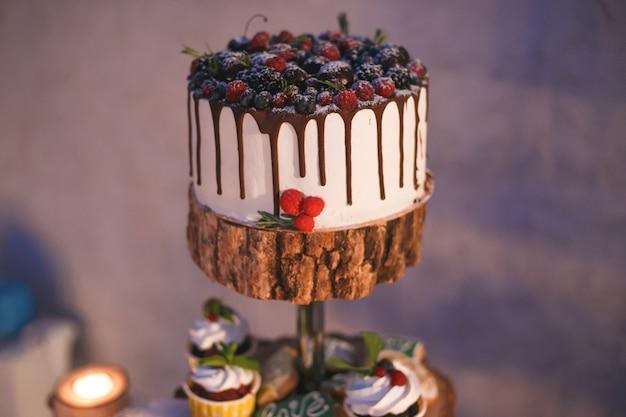 Bolo e cupcakes com frutas em uma prateleira de madeira à luz de velas Foto Premium