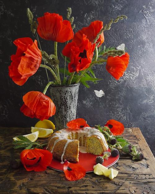 Bolo ligado do limão caseiro e flores vermelhas. borboletas voando Foto Premium