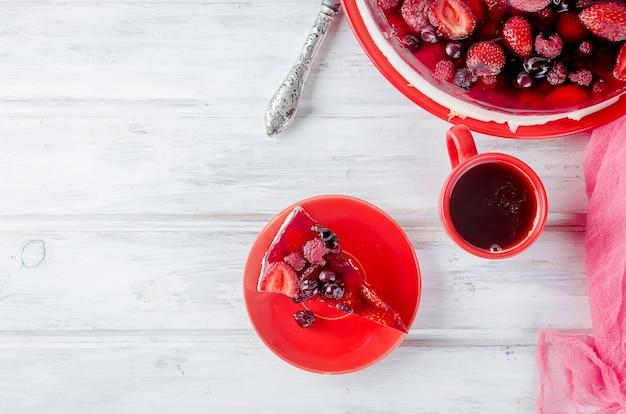 Bolo ou cheesecake com frutas e uma xícara de café Foto Premium
