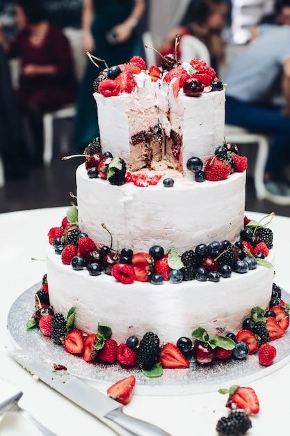 Bolo saboroso de casamento incrível grande com chantilly branco coberto por frutas e bagas suculentas Foto Premium