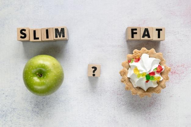 Bolo tart e maçã verde com slim; texto plano em blocos de madeira sobre a superfície texturizada Foto gratuita