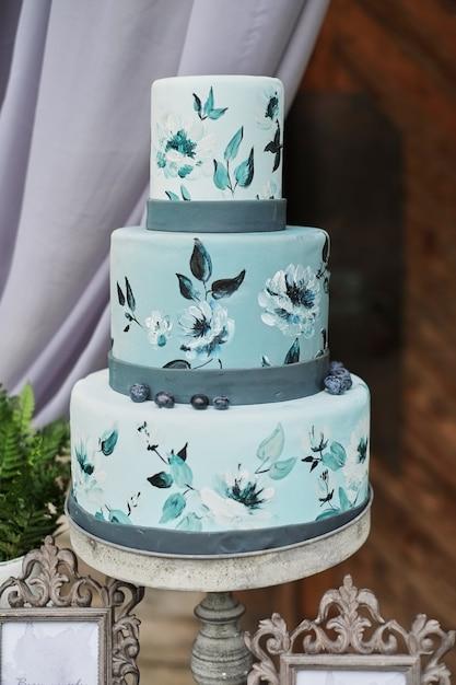 Bolo três-estratificado azul bonito decorado com flores em um suporte, na tabela do casamento. Foto Premium