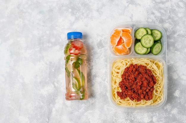 Bolonhesa de espaguete para viagem em uma lancheira de plástico com bebida de desintoxicação e fatia de frutas na luz Foto gratuita