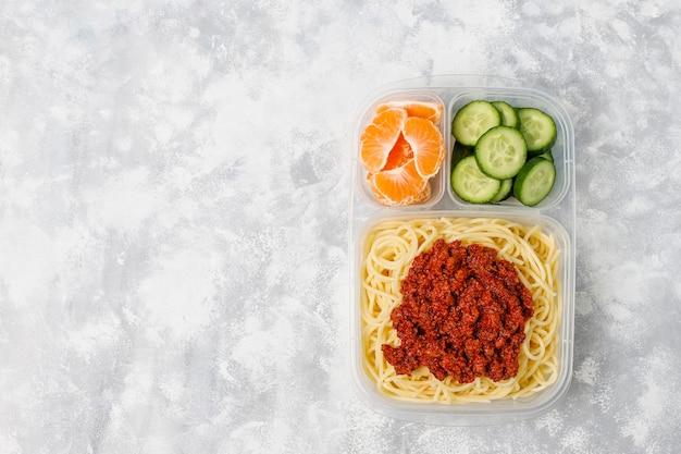 Bolonhesa de espaguete para viagem em uma lancheira de plástico e fatia de frutas na luz Foto gratuita