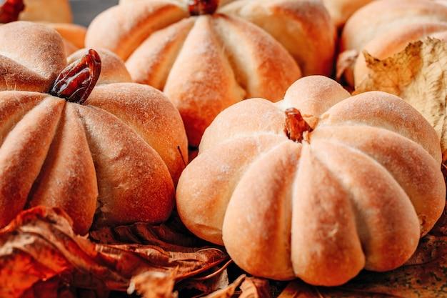 Bolos caseiros em forma de abóbora com folhas de outono close-up. conceito de doces de halloween Foto Premium