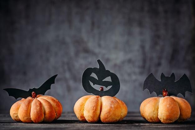 Bolos caseiros em forma de abóbora e halloween decorações em fundo escuro Foto Premium