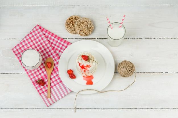 Bolos de arroz branco de vista superior e morangos no prato com toalha de mesa riscada vermelha, colher de pau e laticínios na superfície da placa de madeira branca. horizontal Foto gratuita