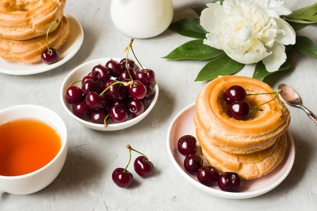 Bolos de creme anel com cereja em um prato em cinza Foto Premium