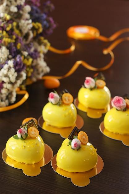 Bolos de mousse brilhantes caseiros corações com revestimento de espelho amarelo em um escuro Foto Premium