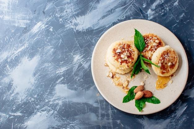 Bolos de queijo com amêndoas hortelã e xarope de bordo em um fundo cinza de uma mesa de concreto. Foto Premium