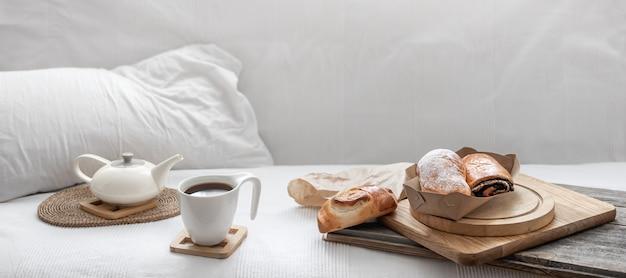 Bolos frescos e uma xícara de café no fundo de uma cama branca. brunch e conceito de fim de semana. Foto gratuita