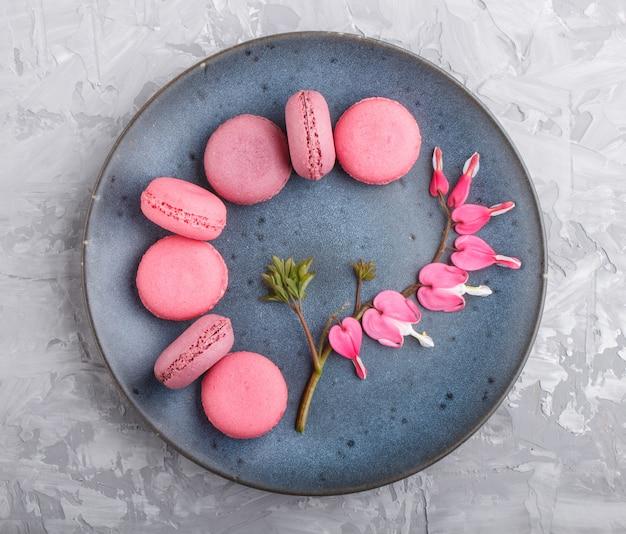 Bolos roxos e cor-de-rosa do macaron ou do bolinho de amêndoa na placa cerâmica azul no fundo concreto cinzento. Foto Premium
