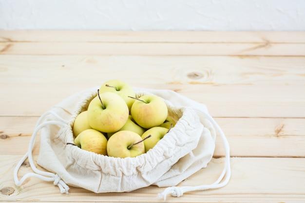 Bolsa de lona com laços com maçãs em um fundo de madeira natural Foto Premium