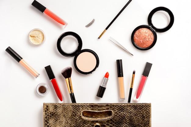 Bolsa de maquiagem de couro, com produtos de beleza cosméticos, derramando sobre fundo branco Foto Premium