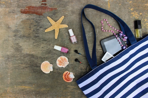 Bolsa de praia, cosméticos e acessórios femininos em madeira velha Foto Premium