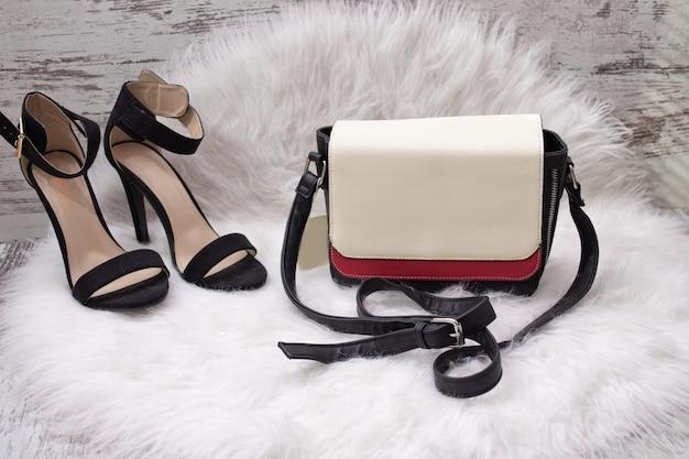 Bolsa feminina branca e vermelha, sapatos pretos com pêlo branco. conceito elegante Foto Premium