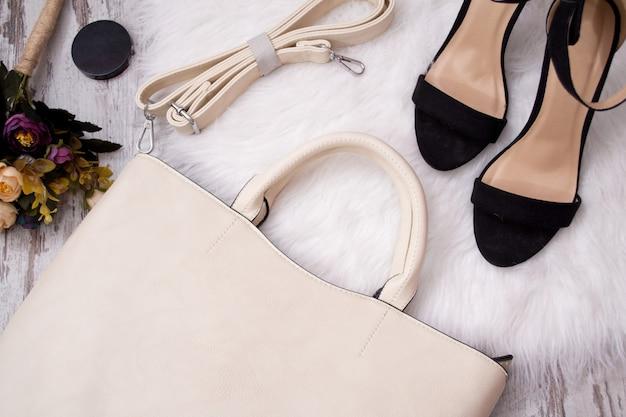 Bolsa leve, sapatos pretos e flores Foto Premium