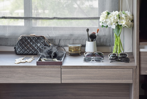 Bolsa, óculos escuros, jóias e pincéis de maquiagem em uma penteadeira de madeira Foto Premium