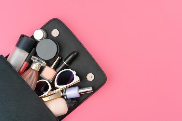 Bolsa pequena feminina cheia de produtos cosméticos em fundo rosa brilhante Foto Premium