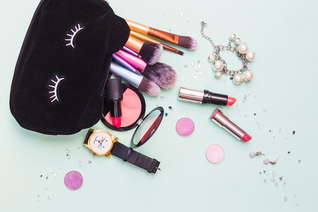 Bolsa preta com pincéis de maquiagem; pulseira; produto de relógio de pulso e cosméticos em fundo pastel Foto gratuita
