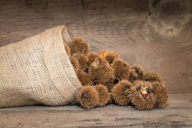 Bolsa que derrama castanhas na madeira rústica Foto gratuita