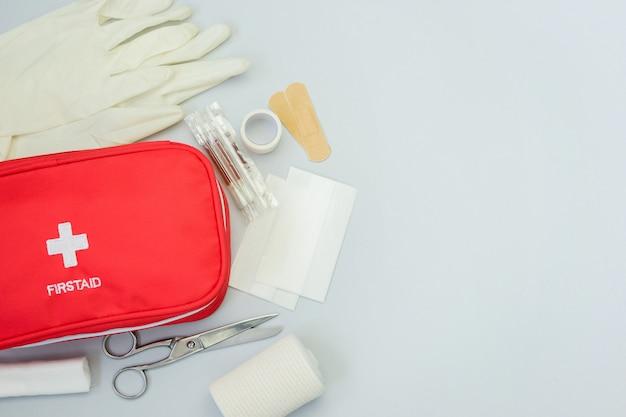 Bolsa vermelha de kit de primeiros socorros com equipamento médico e medicamentos para tratamento de trauma e lesões. vista superior plana leigos em fundo cinza. copie o espaço. Foto Premium