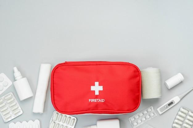 Bolsa vermelha de kit de primeiros socorros com equipamentos médicos e medicamentos para tratamento de emergência. vista superior plana leigos em fundo cinza. copie o espaço. Foto Premium