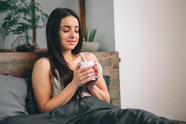 Bom dia a mulher acordou na cama. mulher tomando café na cama Foto Premium