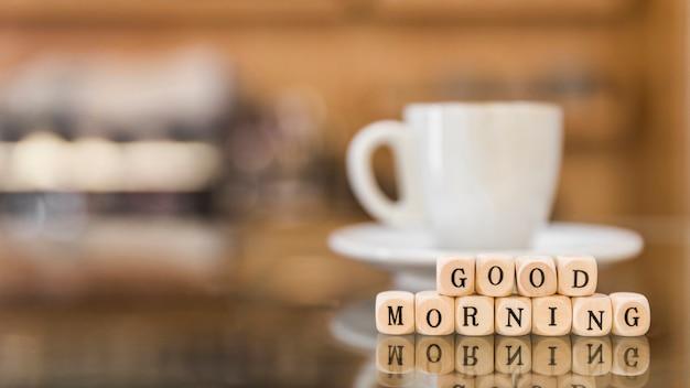Bom dia blocos cúbicos com xícara de café de reflexão sobre o vidro Foto gratuita