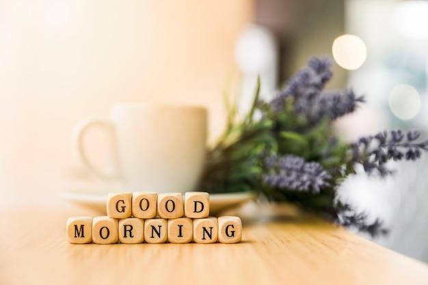 Bom dia blocos cúbicos com xícara de café e flor na mesa de madeira Foto gratuita