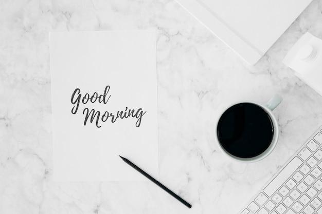 Bom dia escrito em papel branco com lápis; xícara de café; diário; caixa de leite e teclado na mesa texturizada Foto gratuita