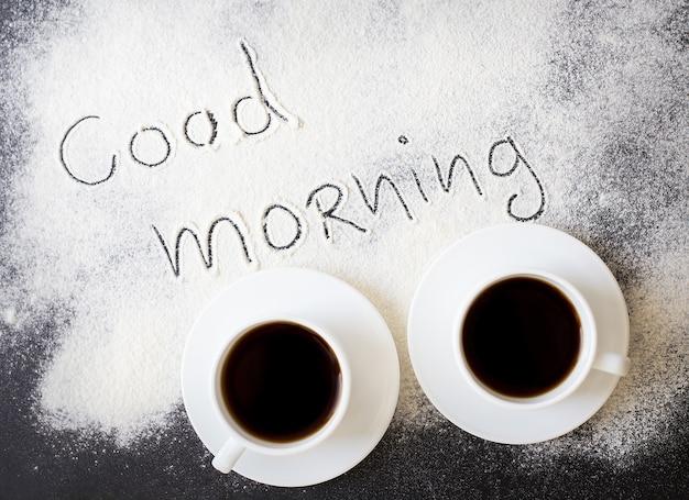 Bom dia inscrição no quadro com farinha e duas canecas de café Foto Premium