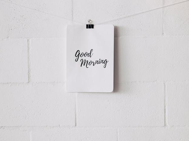 Bom dia tag anexar na seqüência de caracteres com clipe de papel bulldog contra parede branca Foto gratuita