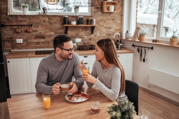 Bom fim de semana. pares milenares positivos que sentam-se na cozinha rústica moderna, bebendo o café da manhã e comendo o café da manhã. Foto Premium