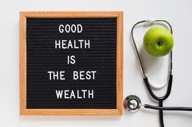 Bom quadro de mensagens de saúde com maçã verde e estetoscópio no fundo branco Foto gratuita