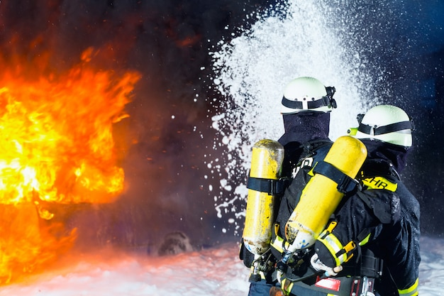 Bombeiro, bombeiros extinguindo um grande incêndio Foto Premium