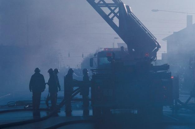 Bombeiros e caminhão de bombeiros, respondendo ao fogo Foto Premium