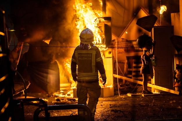 Bombeiros em torno de uma fogueira causada por um falla valenciana controlando as chamas do fogo. Foto Premium