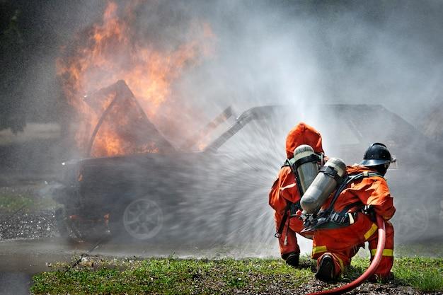 Bombeiros que usam o extintor e a água para o fogo do lutador durante o treinamento do firefight. Foto Premium