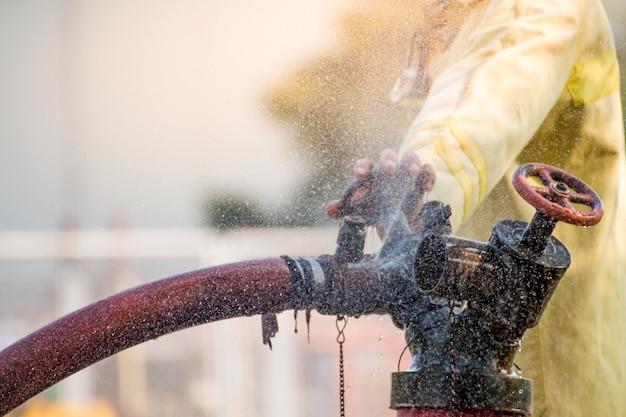 Bombeiros, usando a água da mangueira para combate a incêndio no treinamento de grupo de seguro de combate a incêndio bombeiro, vestindo um traje de fogo para a segurança sob o caso de treinamento de perigo. Foto Premium