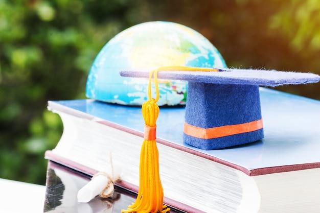 Boné de formatura azul no livro com borrão do globo do mundo de terra de américa Foto Premium