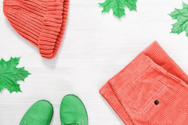 Boné de malha laranja feminino, calças e botas de couro em fundo branco de madeira com folhas de plátano e com espaço de cópia. conceito de outono e moda com roupas quentes tendência cor. vista do topo. Foto Premium