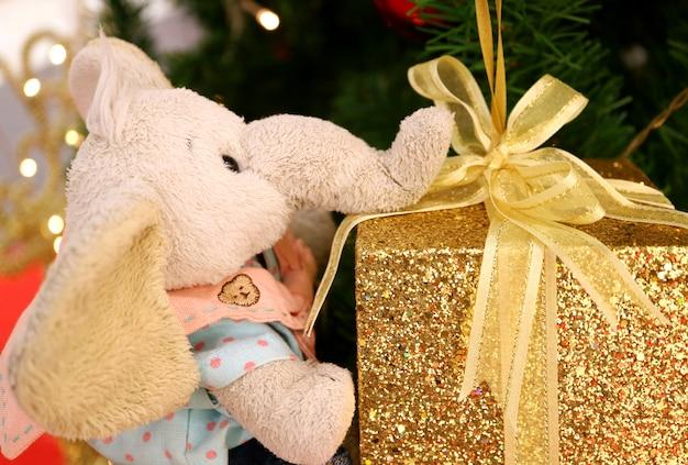 Boneca elefante fofo segurando a caixa de presente de glitter dourados com laço de fita de ouro Foto Premium