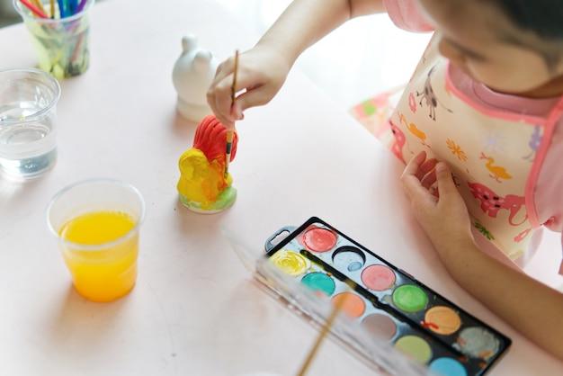 Bonecas animais do emplastro da pintura asiática pequena nova da menina na classe de pintura em casa. Foto Premium