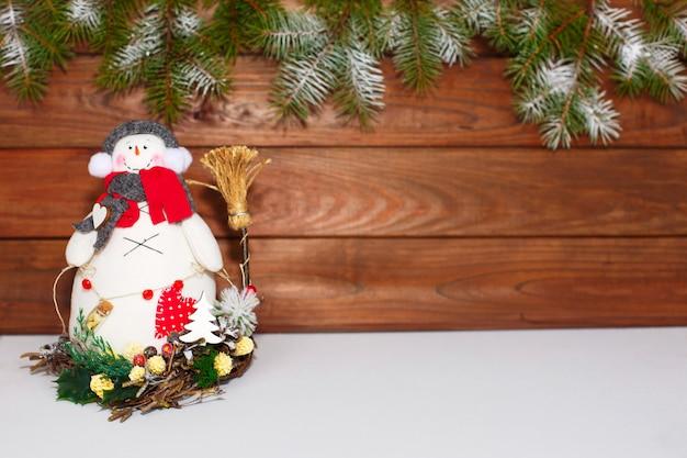 Boneco de neve de natal feliz. decoração de natal em um fundo de madeira. cartão de saudação decoração de natal. Foto Premium