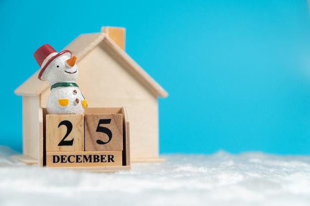 Boneco de neve sentado no calendário de bloco de madeira definido em 25 de dezembro em lã branca na frente de madeira Foto Premium