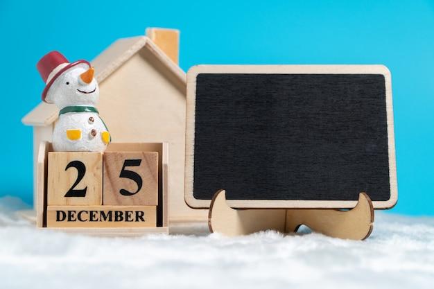 Boneco de neve sentado no calendário de bloco de madeira definido em 25 de dezembro Foto Premium