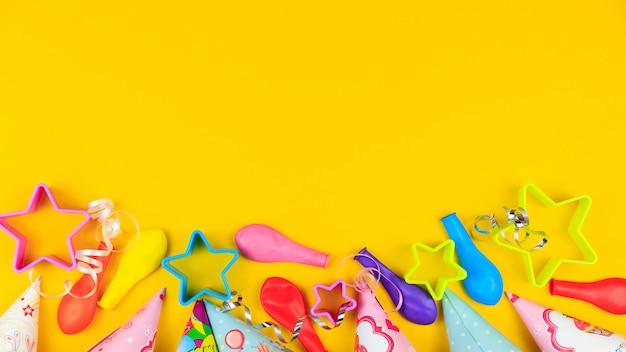 Bonés de festa de aniversário, balão e estrelas em fundo amarelo Foto Premium