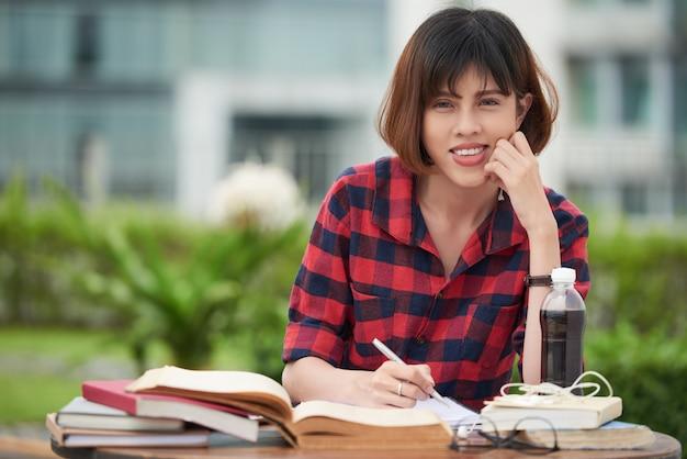 Bonita aluna se preparando para o exame ao ar livre Foto gratuita